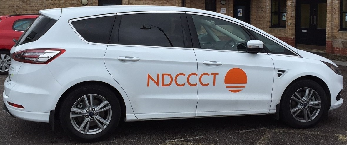 A white Cancer Care car outside the Go North Devon office with a driver sat in drivers seat.