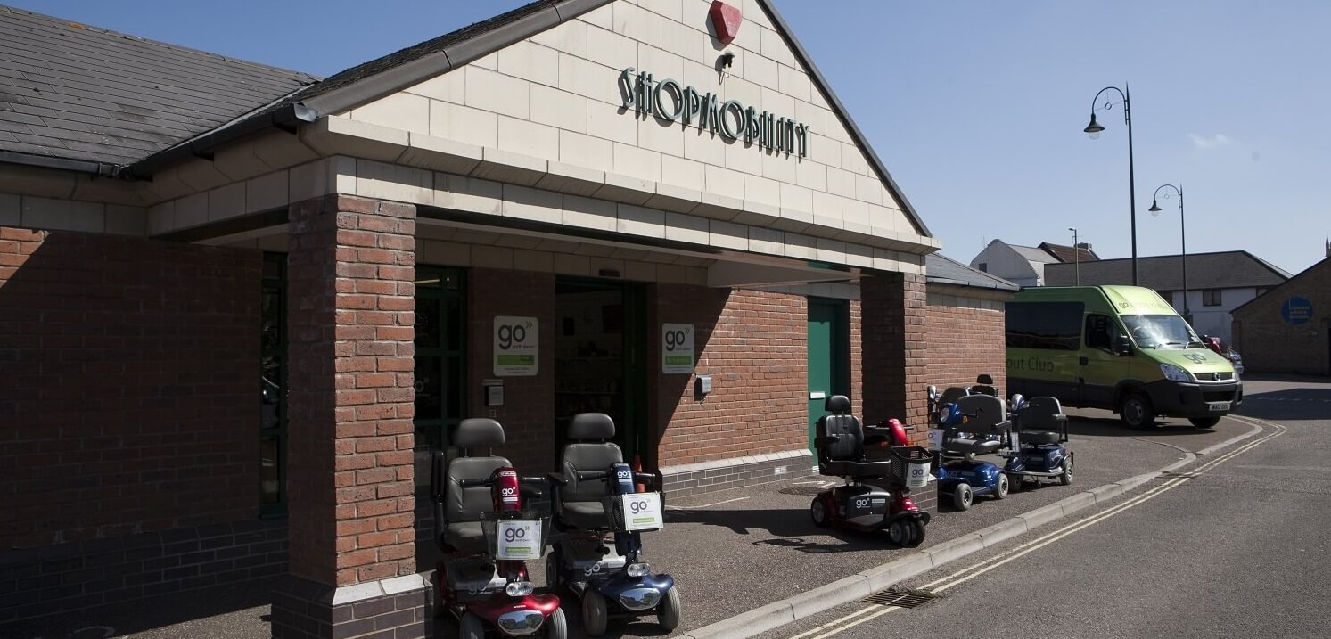 The Shopmobility Centre with scooters outside the front door and Out and About club bus.