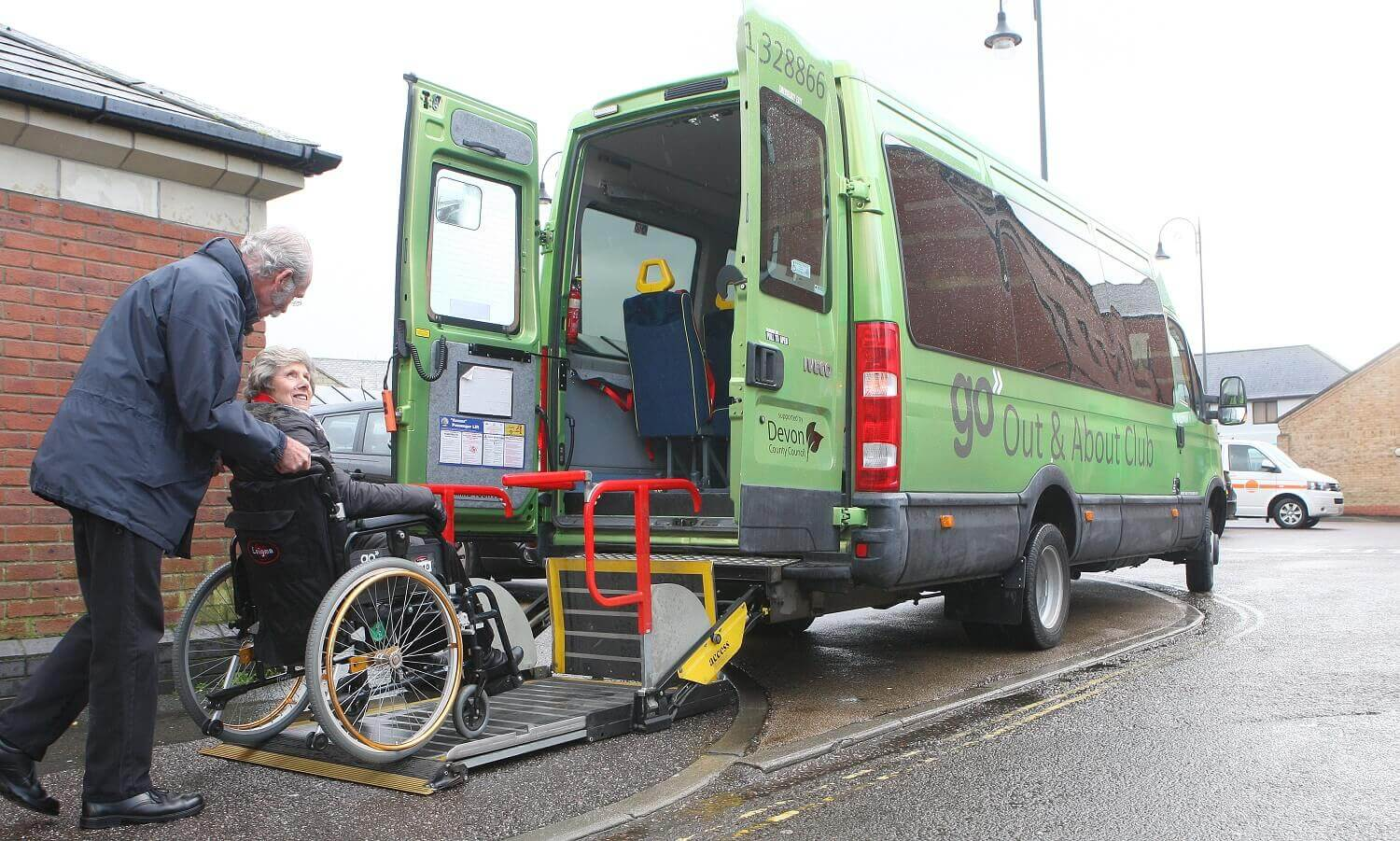 A Go North Devon driver assisting an elderly lady in a wheelchair on a bus via the accessibility lift.