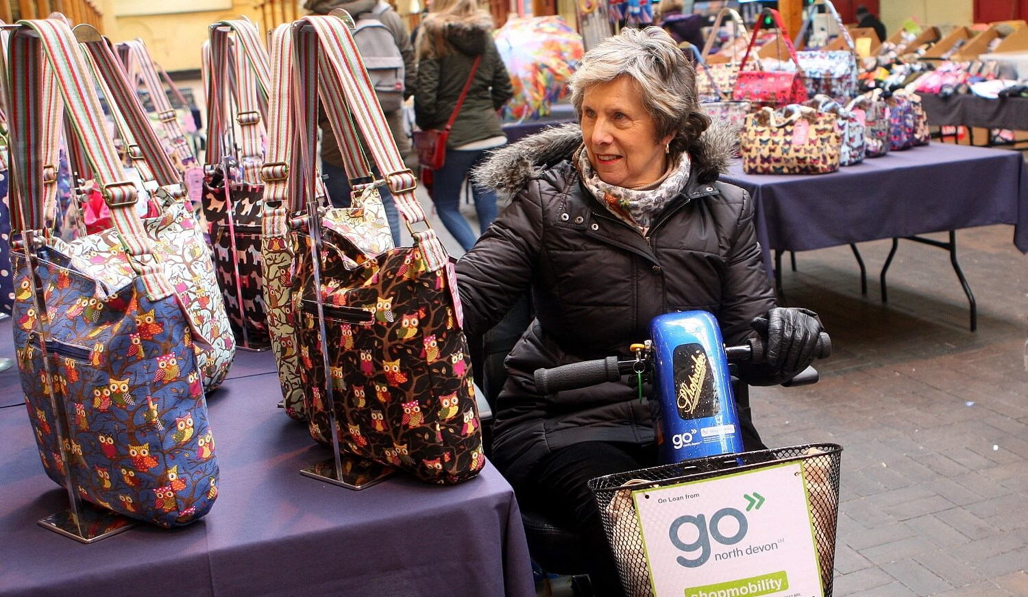 An elderly lady browsing handbags in a market on a Go North Devon shopmobility scooter.